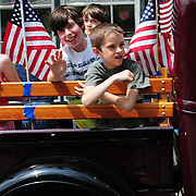 BATH -- 5/25/15 - Isaac Ensel, left and Drew and Gideon Walden, all of Bath, ride in the back of representative Jennifer DeChant's truck during the The Memorial Day Parade in Bath on Monday. <br /> The parade took place as a result of an anonymous donor who gave $5,000 and the American Legion who donated $3,000 to pay for the parade in Bath. The Elks Club supported the parade in prior years but was unable to do so this year, leaving organizers without a funding source close to the parade date.  <br /> Photo ©2015 by Roger S. Duncan / For the Forecaster.