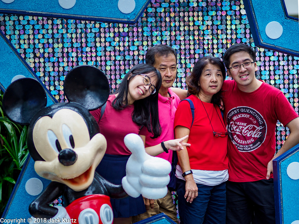 """12 DECEMBER 2018 - SINGAPORE: A family poses for a photo with Mickey Mouse at a Christmas display on Orchard Road. Orchard Road is the main shopping district of Singapore and for years hosts a large light display around Christmas. The main sponsor of this year's display is the Disney Company and the displays are decorated with characters from the Disney entertainment universe. This has upset some religious leaders in Singapore and the National Council of Churches of Singapore (NCCS) sent a letter to the Singapore Tourism Board (STB) expressing its concern about the """"increasing secularisation and commercialization of Christmas"""" in Singapore. The STB reached out to the NCCS, but the Orchard Road lights will remain on through the holidays.   PHOTO BY JACK KURTZ"""