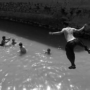 Afghan children swim, bath and play in a canal in the heart of Kandahar City, Afghanistan. Most residents of Kandahar have no runing water and rely on canals and wells for their water needs. Many residents in Kandahar have very little access to basic utilities as the infrastructure of the city has collapsed under the weight of years of conflict and poverty. (Credit Image: © Louie Palu/ZUMA Press/The Alexia Foundation).Sept. 15, 2010.Photograph taken on film exact date estimated and not known.....