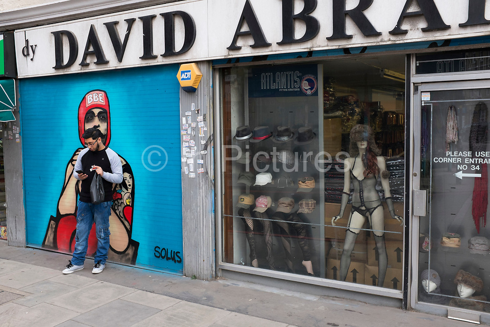 Scene outside a strange looking clothing and hat store in Whitechapel, East End London, UK. In the shop window are hats, legs wearing tights, and a fur hat wearing mannequin in a sexy fishnet underwear outfit. A truly bizarre and eclectic mix.
