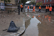 Waters subside leaving a mess of silt and stones after a Thames Water main water main burst on 25th October 2016, Camberwell New Road, Southwark, London. Thames Water officials, inspectors and police inspect the damage to the A202 Camberwell New Road now closed to traffic after the overnight event.