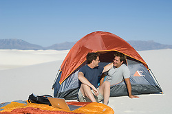 Gay couple being affectionate while camping out in White Sands, New Mexico