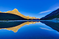 Alpenglow on the mountain peaks surrounding Lower Waterfowl Lake at Sunrise with the mountains reflected the glassy calm waters of the lake.<br /> <br /> ©2015, Sean Phillips<br /> http://www.RiverwoodPhotography.com