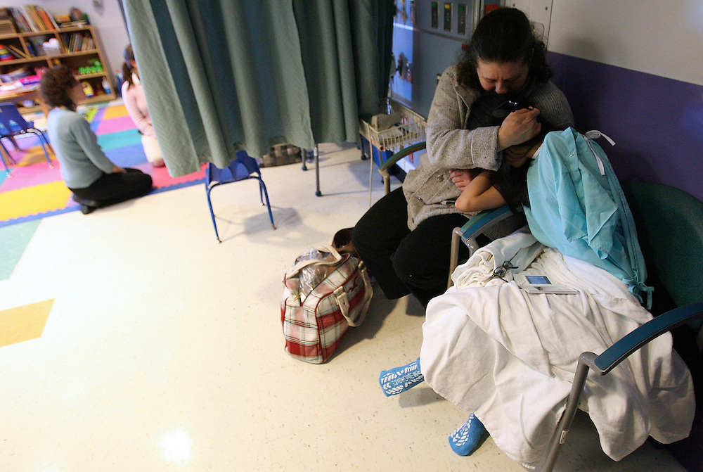 """2/13/2009 Baltimore, MD-  Lani Dickinson, 14, is comforted by her mother Julie Bell in a waiting room at Johns Hopkins Hospital before she undergoes surgery for the """"revision of her transhumeral amputation.""""  Lani was born in China with a congenital defect and adopted by an American family.  Despite her disability, she trains hard as a ballerina and would like to someday be a professional dancer.  Photo by Lisa Hornak"""