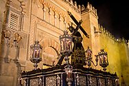 A float with a large statue of Jesus Christ passes by the Mezquita, the cathedral of Cordoba, originally built as a mosque during the Arabic era. Andalusia, Spain