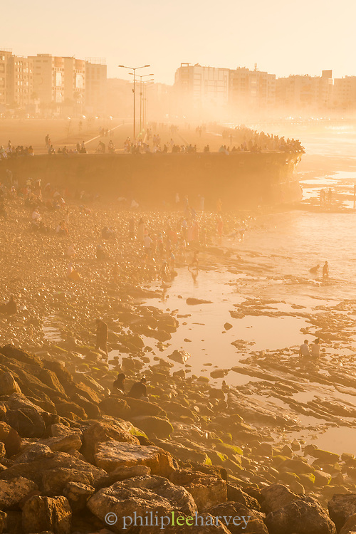 Silhouettes of tourists on stony beach at sunset, Casablanca, Morocco