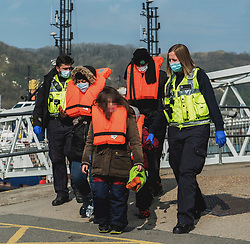 **Image pixelated to hide identity of children**<br /> © Licensed to London News Pictures. 24/03/2021. Dover, UK. A family being escorted form a boat at Dover, Kent by Border Force officers. Home Secretary Priti Patel has pledged an overhaul of asylum seeker rules, with refugees having their claim assessed based on how they arrive in the UK. Photo credit: Stuart Brock/LNP