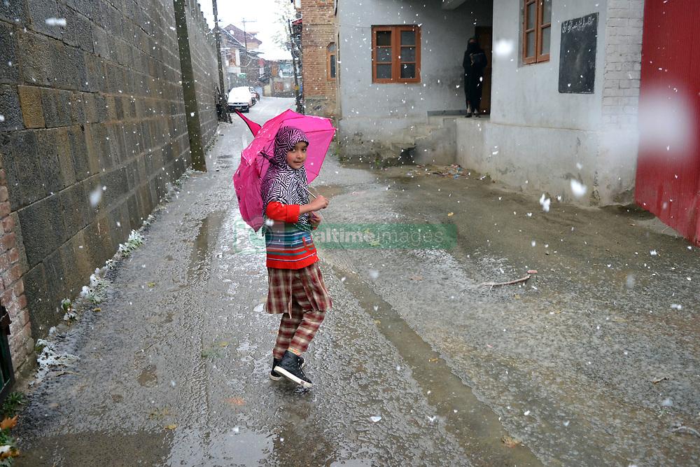 A Kashmiri young  walks briskly amid snowfall in Srinagar, the summer capital of Indian controlled Kashmir. Kashmir witnessed its first snowfall.