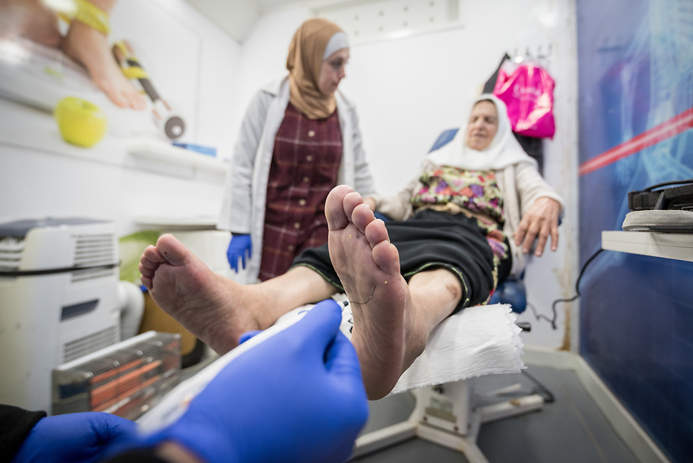 26 February 2020, Abu Dis, Palestine: Nurse Najwa Hawamdeh administers a foot exam as 87-year-old Diabetes patient Hamama Jaffal from Abu Dis visits the Augusta Victoria Hospital's Mobile Diabetes Clinic. Here, testing the sensitivity of her feet through a monofilament sensitivity test. In an effort to make Diabetes services more accessible to people in the West Bank, the Augusta Victoria Hospital offers a Mobile Diabetes Clinic, which moves around to various locations in the West Bank, offering screening and routine testing for Diabietes and the symptoms it causes.