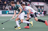 AMSTELVEEN -  Guus Jansen (Rotterdam) met Bram Huijbregts (Amsterdam) tijdens de competitie hoofdklasse hockeywedstrijd heren, Amsterdam -Rotterdam (2-0) .  COPYRIGHT KOEN SUYK