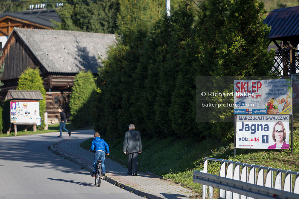 As a young boy pedals uphill, he passes a local elderly gentleman walking to morning mass at the nearby Greek-Catholic Jana Chrzciciela church, on 22bd September 2019, in Jaworki, near Szczawnica, Malopolska, Poland.
