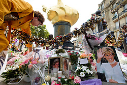 © Licensed to London News Pictures. 31/08/2017. Paris, France. A woman arranges flowers next to tributes to the late Princess Diana above the Post de l'Alma tunnel in Paris. Princess Diana died with Dodi Al-Fayed in a car crash on 31st August 1997. Photo credit: Ray Tang/LNP