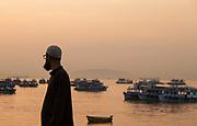 Rear view of man in traditional muslim dress, Mumbai Harbor, Mumbai, India