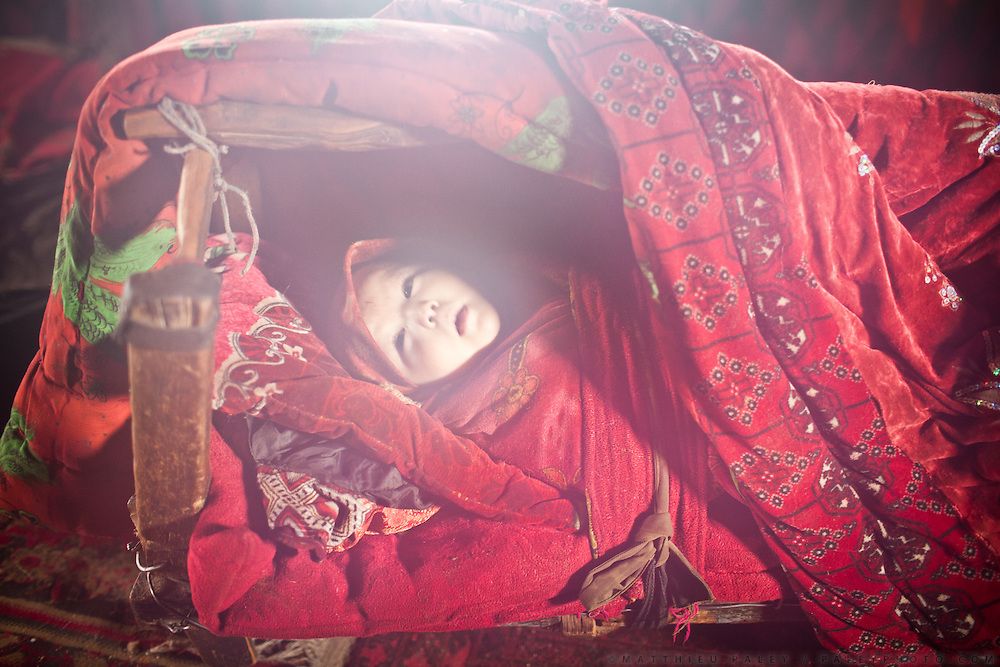 Kyrgyz Baby..The Afghan Pamir region has the world's highest child mortality rate (52% of kids before the age of 5 die). Kids born in winter have less chance of survival that those born in summer. .Kyzyl Qorum, campment of the former late Khan, Abdul Rashid Khan.
