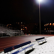 High school football stadium at night covered in a light snow with floodlights