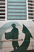 The graphic showing a person delivering a package, on the side of a couriers van, passing beneath corporate offices in the City of London, the capitals financial district, on 4th February 2020, in London, England. A man wearing a peaked cap is shown carrying a box with a large arrow pointing upwards to nearby offices.