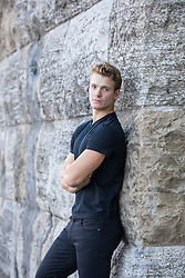 sexy blond young man in a black tee shirt leaning against a stone wall