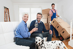 Senior couple celebrating moving to new house with champagne, Bavaria, Germany