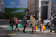 Women shoppers carrying matching bags, walk on New Bond Street with a Dior construction hoarding behind.