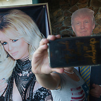 A customer takes a picture of herself with a poster of Stormy Daniels and cutout of President Donald Trump while waiting to enter Stars Cabaret in Bend on Thursday.