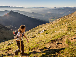 Girl walking on single trail towards hill