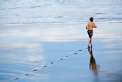 Boy running across the beach; Las Palmas; Canaries,