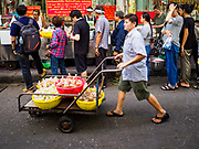 """18 MAY 2017 - BANGKOK, THAILAND: A woman deivers curry to Jek Pui curry stand, a popular street food stall for curry dishes. The curry is prepared in a family kitchen about one block away. City officials in Bangkok have taken steps to rein in street food vendors. The steps were originally reported as a """"ban"""" on street food, but after an uproar in local and international news outlets, city officials said street food vendors wouldn't be banned but would be regulated, undergo health inspections and be restricted to certain hours on major streets. On Yaowarat Road, in the heart of Bangkok's touristy Chinatown, the city has closed some traffic lanes to facilitate the vendors. But in other parts of the city, the vendors have been moved off of major streets and sidewalks.      PHOTO BY JACK KURTZ"""