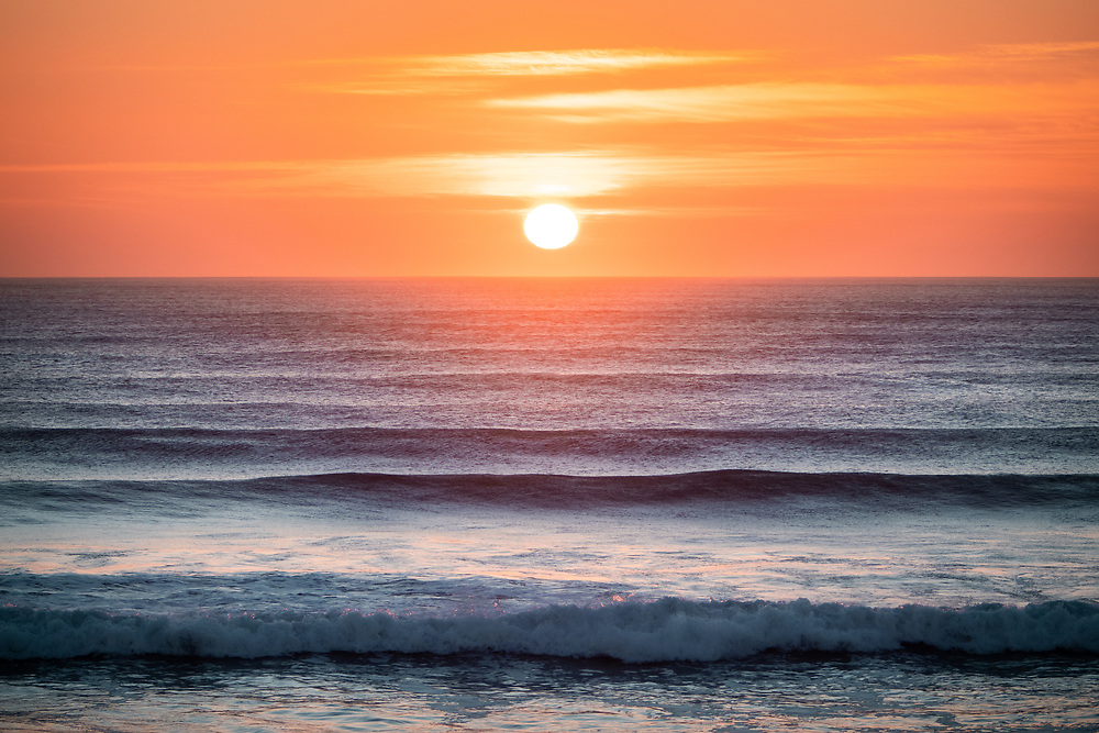 Sun setting in an orange sky over the waves at St Ouen's Bay, Jersey, Channel Islands