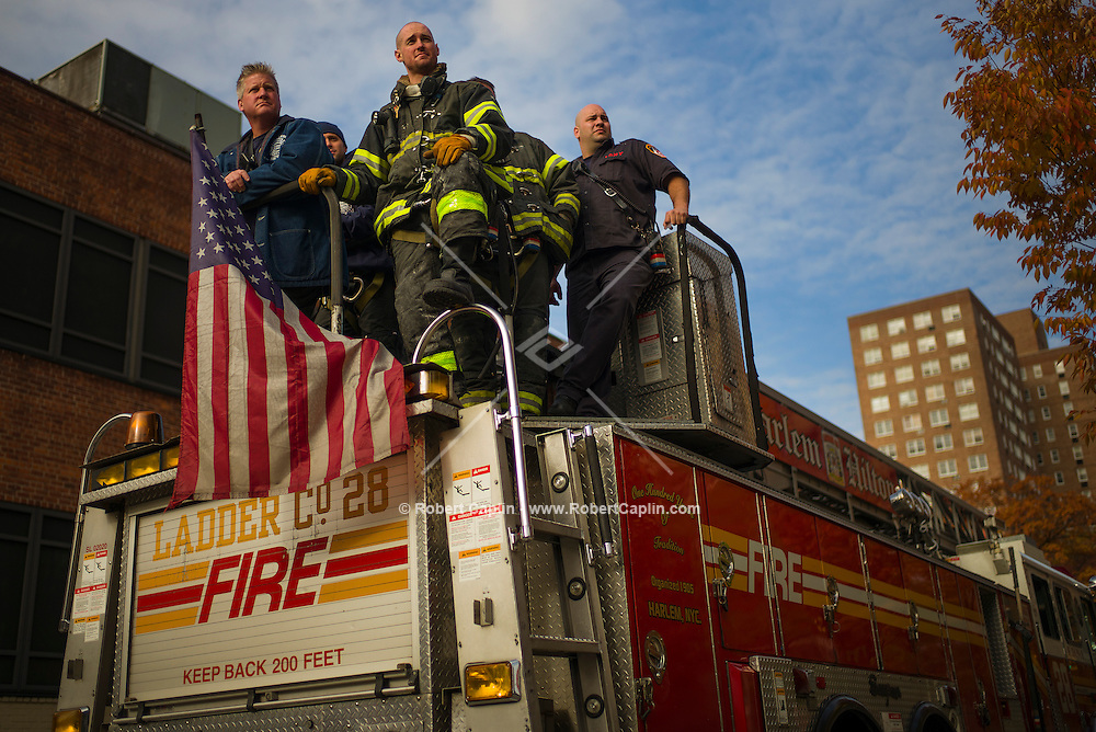 NEW YORK, NY – NOVEMBER 3, 2013: Firefighters of Ladder 28 in Harlem cheer Marathon runners on during the 2013 New York City Marathon in Harlem as they runners exit the Madison Avenue Bridge back into Manhattan from The Bronx.  <br /> <br /> Photo by Robert Caplin