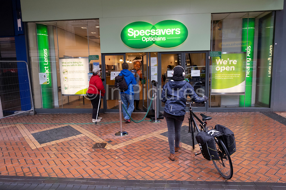National coronavirus lockdown three begins on New Street in Birmingham city centre, which is deserted apart from a few people outside Specsavers in an area which is normally busy with shoppers on 6th January 2021 in Birmingham, United Kingdom. Following the recent surge in cases including the new variant of Covid-19, this nationwide lockdown, which is an effective Tier Five, came into operation today, with all citizens to follow the message to stay at home, protect the NHS and save lives.