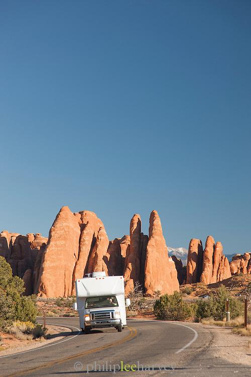 RV (caravan) driving through a desert landscape, Arches National Park, Utah, United States of America