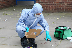 © Licensed to London News Pictures. 31/03/2019. London, UK. A Forensic Officer collects the victim's mobile phone at the crime scene on Fore Street in Edmonton, north London where a person was stabbed just after 9.30am this morning. The victim was taken to a hospital by Air Ambulance and his condition is unknown. Photo credit: Dinendra Haria/LNP