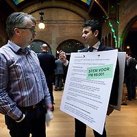 Nederland, Amsterdam , 8 februari 2014.<br /> D66 congres in Beurs van Berlage.<br /> Op de foto: Man met verkiezingsbord in gesprek met partijgenoot.<br /> Foto:Jean-Pierre Jans