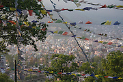 The houses and haze of Kathmandu, Nepal, as seen through prayer flags outside Swayambhunath Temple.