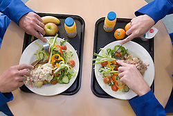 Men eating lunch from trays in the work canteen,