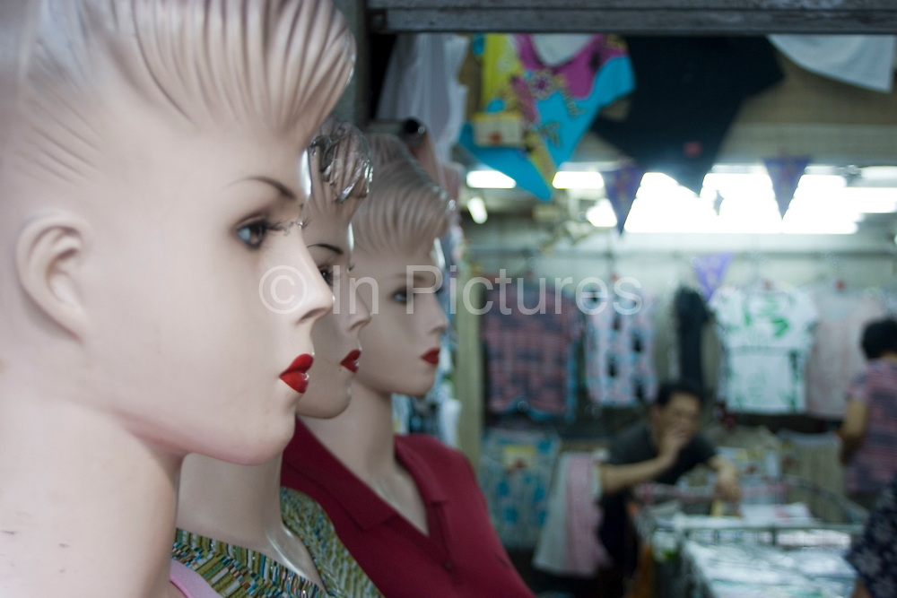 Female showroom dummies at a textiles shop in downtown Shanghai. This style of western dummy with sculpted hair, bright red lips and dark eye make up is common throughout the city, and can be seen all over China. This choice of western model interestingly reflects the desire for western looks and light skin common amongst Chinese women in particular.