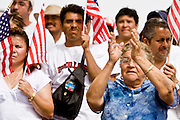 10 APRIL 2006 - PHOENIX, AZ: People cheer at an immigration reform rally in Phoenix, AZ. More than 200,000 people participated in a march for immigrants's rights in Phoenix Monday. The march was a part of a national day of action on behalf of undocumented immigrants. There were more than 100 such demonstrations across the US Monday. Protestors were encouraged to wear white, to symbolize peace, and wave American flags, to demonstrate their patriotism to the US.  Photo by Jack Kurtz