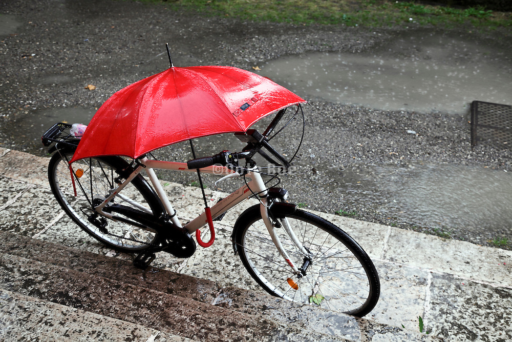 bicycle with red umbrella during a heavy rain storm