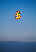 John Ninomiya, a cluster balloonist rises to 4500 feet above the San Joaquin valley near Coalinga, California site of the 37th annual Whamobass (Whiskey Hill, Atherton, Menlo Oaks Ballooning and Sporting Society, the longest continuously running ballooning festival in the world.  Cutting Balloons away to descend and dumping water from water containers by his side to rise Ninomiya can control his altitute and to an extent, his direction of travel.