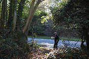 A country walker checks his Ordnance Survey map on a footpath alongside the A20 road, on 21st October 2018, near Hollingbourne, Kent, England.