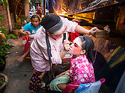 16 JANUARY 2015 - BANGKOK, THAILAND: Performers with the Sai Yong Hong Teochew Opera Troupe help each other get ready for a performance at the Chaomae Thapthim Shrine, a Chinese shrine in a working class neighborhood of Bangkok near the Chulalongkorn University campus. They don't have dressing rooms per se, instead setting up their make up tables right on the sidewalk. The troupe's nine night performance at the shrine is an annual tradition and is the start of the Lunar New Year celebrations in the neighborhood. Lunar New Year, also called Chinese New Year, is officially February 19 this year. Teochew opera is a form of Chinese opera that is popular in Thailand and Malaysia.    PHOTO BY JACK KURTZ