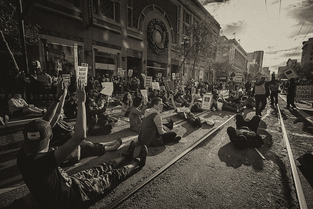 Demonstrators stage a die-in in the middle of the road in busy Downtown San Francisco, outside the Westfield Shopping Centre.