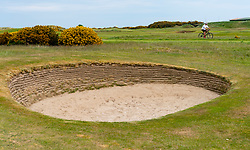 Man cycles past bunker on Old Course at St Andrews Scotland, UK during covid-19 lockdown, Scotland, UK
