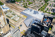Nederland, Zuid-Holland, Rotterdam, 10-06-2015; dak, perron en sporen van het gerenoveerde en volkomen vernieuwde station van Rottterdam, Rotterdam CS. Rechts het gebouw Delftse Poort van NN Group (Nationale Nederlanden), sponsor van de Marathon Rotterdam. Het spoorwegstation, bijnaam De Kapsalon is ontworpen door Benthem Crouwel Architekten.   <br /> The roof of the completely renovated railway station Rottterdam, Rotterdam Central (Benthem Crouwel architects) and is nicknamed The Hair Salon. <br /> luchtfoto (toeslag op standard tarieven);<br /> aerial photo (additional fee required);<br /> copyright foto/photo Siebe Swart
