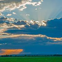 The sun sets behind a thunderstorm rain squall in Gallatin Valley near Bozeman, Montana.
