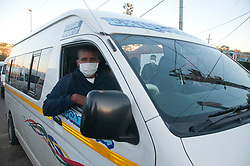 A taxi driver wearing a mask at the wheel of his taxi.
