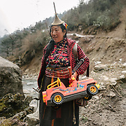 A Layap woman carries a plastic toy Made in China up to the Laya village. On the trek going from Laya village to the beginning of the drivable road.