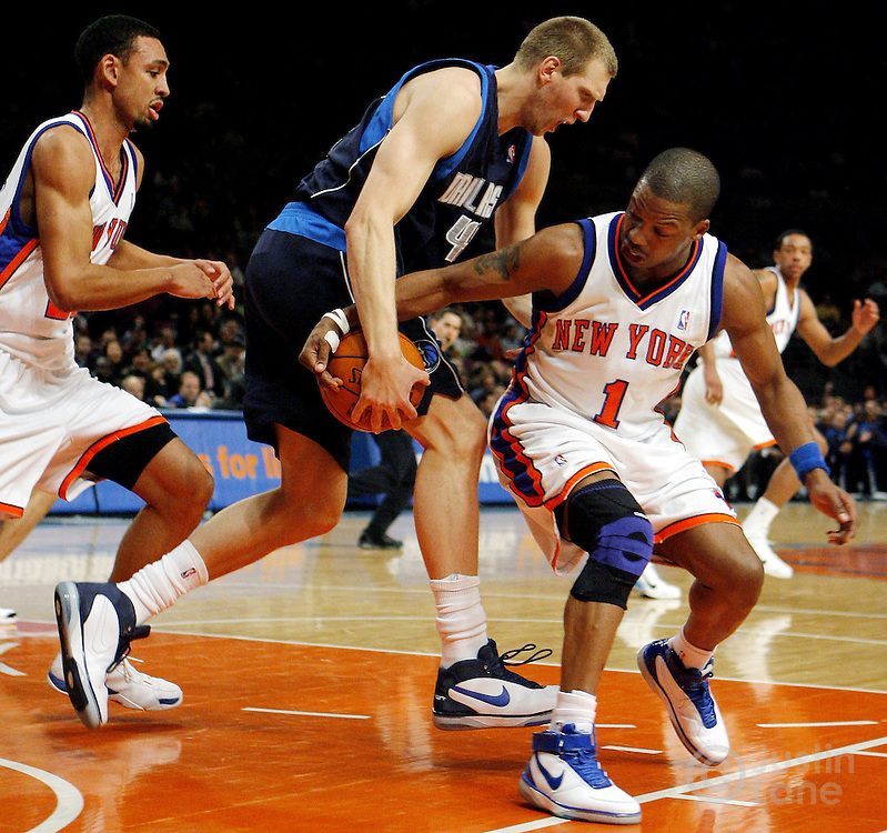The Knicks' Steve Francis (R) tries to steal the ball from the Mavericks' Dirk Nowitzki (C)  during the first half of the game between the Dallas Mavericks and the New York Knicks at Madison Square Garden in New York, New York on Tuesday 20 March 2007. At left is the Knicks' Jared Jefferies.