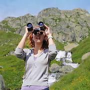 Girl with binoculars in ALpine mountains
