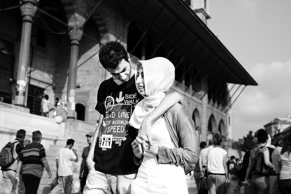 A young couple passing by the New Mosque in Istanbul.